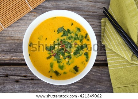 thai yellow curry soup with cilantro on rustic table - stock photo