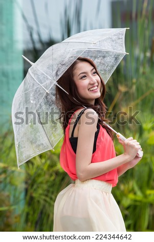 Thai yong girl holding umbrella in the outside - stock photo