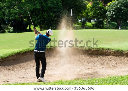 Thai young man golf player in action swing in sand pit during practice before golf tournament at golf course