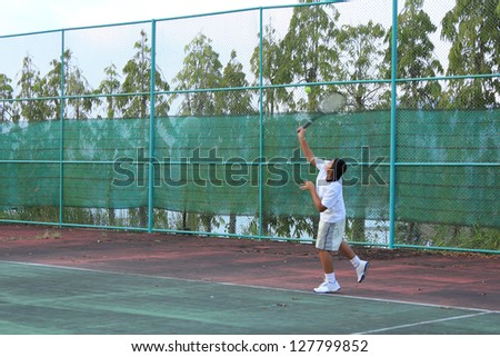 Thai young tennis player serving the ball - stock photo