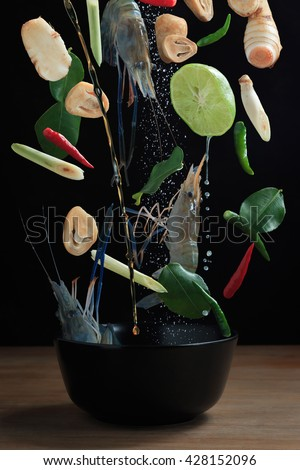 """thaifood """"Tom Yam Kung"""" food falling, flying traditional cuisine in Thailand on wooden background - stock photo"""