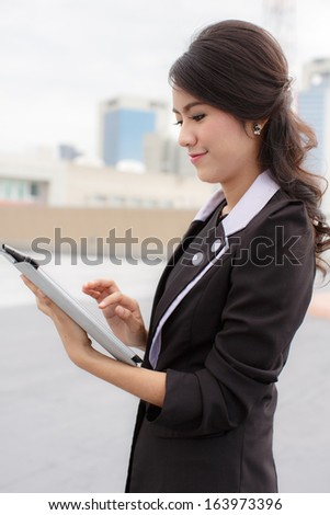 Thailand business woman on the building using ipad tablet pc computer reading ebook - stock photo