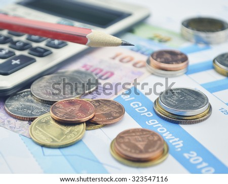 Thailand coins, banknotes, calculator and pencils on business graph, accounting background - stock photo