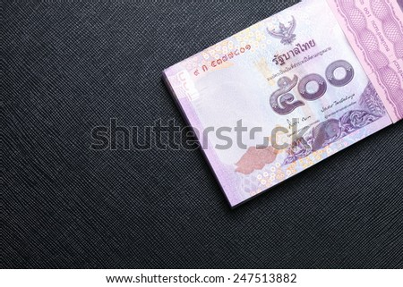 Thailand five hundred baht banknotes put on the black color leather background represent the Thai financial and monetary  related. - stock photo