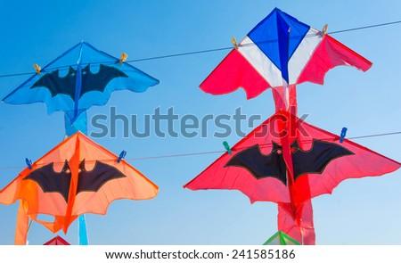 Thailand flag kite and bat kites against cloudless blue sky - stock photo