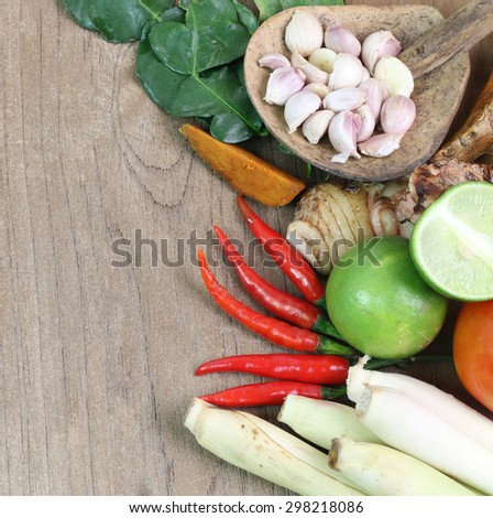 Thailand Food Ingredients: lemon, lime, galangal, ginger ,, tomato, mango leaves the dungeon, garlic on a wooden floor. - stock photo