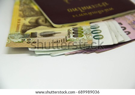 Thailand international traveling passport and baht money over white background. Not isolated. Have space to write text.