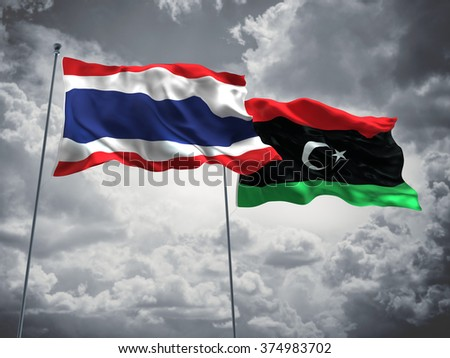 Thailand & Libya Flags are waving in the sky with dark clouds - stock photo