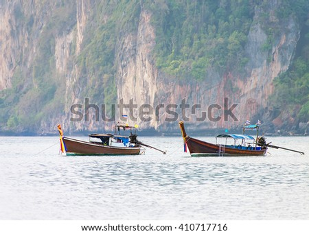 Thailand Loh Damah Beach bay with traditional longtail boats and high rocks, Phi Phi Don island, Krabi Province, Andaman Sea - stock photo
