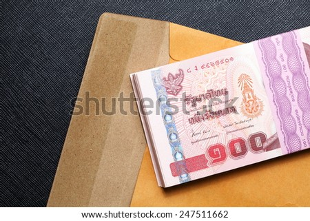 Thailand one hundred baht banknotes put on the brown color paper envelope represent the Thai financial and monetary  related. - stock photo