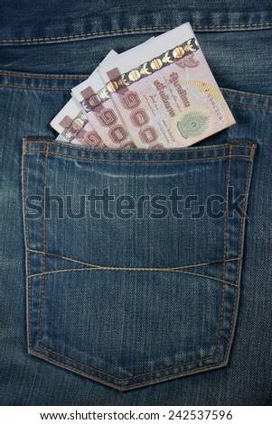 Thailand passport and Thai money in jeans pocket. - stock photo