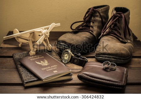 Thailand passport and traveler set on wood background, vintage and retro style.