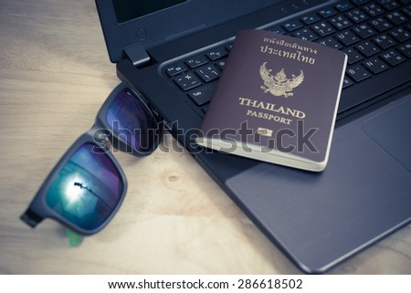 Thailand passport with laptop on table