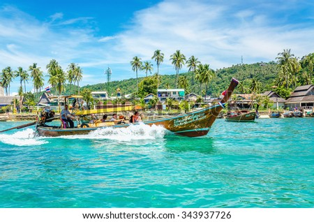 THAILAND, PHI PHI ISLANDS - NOVEMBER 1, 2014: Exotic view of a long tail boata on the coast of Phi Phi Don, bringing the tourists to the most attractive places the archipelago, Thailand, Asia
