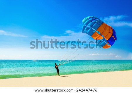 THAILAND, PHUKET - NOVEMBER 2, 2014: Thai man taking off with parasail on sunny beach of Phuket, Thailand - stock photo