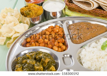 Thali - South Asian selection of vegetarian curries served in a traditional dish with rice, chapatis, poppadoms, yoghurt and chili sauce. - stock photo