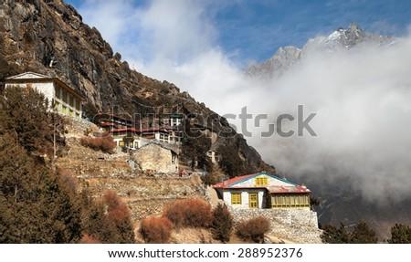 Thame gompa with prayer flags and buddhist symbols - monastery in Khumbu valley on three passes trek, Mount Everest area, Sagarmatha national park, Nepal - stock photo