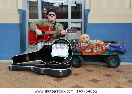 THAMES - AUGUST 13: Street busker playing the guitar with his dog in the main street on August 13, 2013 in Thames, New Zealand. - stock photo