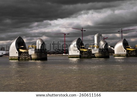 Thames Barrier; Thames Barrier under a threatening sky. Good copy-space  over sky and water  - stock photo