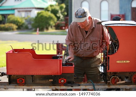 THAMES - MAY 19: Train driver tinkering with his engine at the Thames Small Gauge Railway annual open day on May 19, 2013 in Thames, New Zealand. - stock photo