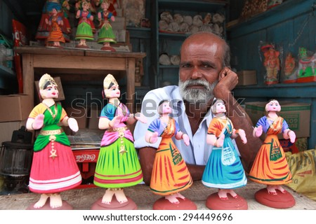 THANJAVUR, INDIA -JUL 31 :An unidentified man sells Tanjore dancing dolls on July 31, 2012 in Thanjavur, India. Dancing dolls of Tanjore are very popular and is widely used in the Navarathri festivals - stock photo