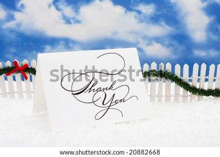 Thank you card sitting on snow with white fence and green garland on a sky background, nutcracker - stock photo