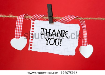 Thank You message written on a paper hanging on the clothesline on red background with two paper hearts - stock photo