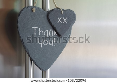 Thank you note written in chalk on a slate heart hanging on a refrigerator door - stock photo
