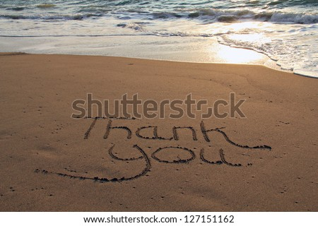 Thank you written in the sand on the beach. - stock photo