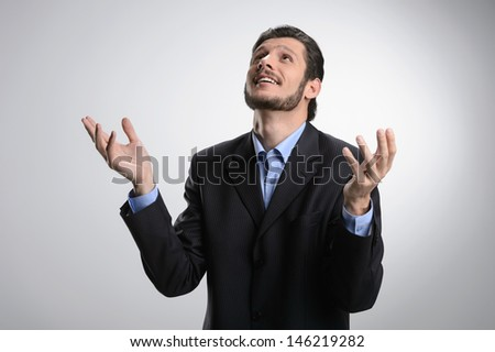 Thanking God. Cheerful bearded man in formalwear standing with his hands raised up while isolated on grey - stock photo
