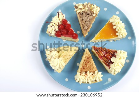 Thanksgiving apple, pecan, cherry, caramel, pumpkin spice and chocolate cream cheesecake pie, on blue polka dot platter against a white table, with copy space. - stock photo