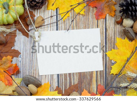 Thanksgiving border of autumn leaves, bare twigs, pinecones, wheat stalks and nuts with rustic wooden background and blank tag with copy space in center. - stock photo
