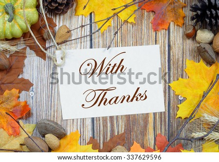 Thanksgiving border of autumn leaves, bare twigs, pinecones, wheat stalks and nuts with rustic wooden background in center. Happy Thanksgiving message included. - stock photo