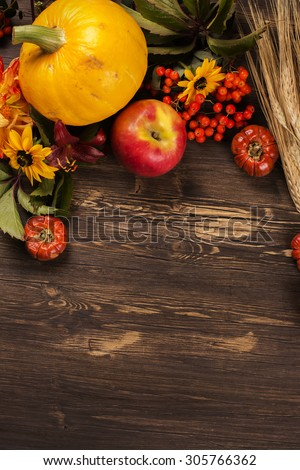 Thanksgiving day or halloween greeting card. Autumn concept. Harvest concept: wheat, vegetables, fruits, berries and flowers on wooden brown table. Selective focus. Toned image. Space for text - stock photo
