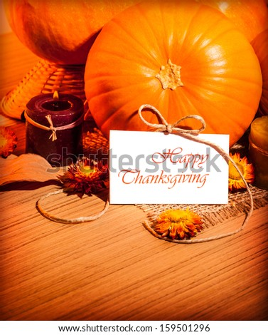 Thanksgiving day still life on wooden table, autumnal holiday, ripe orange gourd with candle and dry flowers, greeting card, harvest season concept