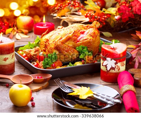 Thanksgiving Dinner. Roasted turkey garnished with Potato, Vegetables and cranberries on a rustic style table decorated with autumn leaves and candles.  - stock photo