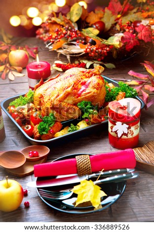 Thanksgiving Dinner. Thanksgiving table served with turkey, decorated with bright autumn leaves. Roasted turkey, table setting. Vertical photo  - stock photo