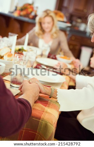 Thanksgiving: Family Praying Before Holiday Dinner - stock photo
