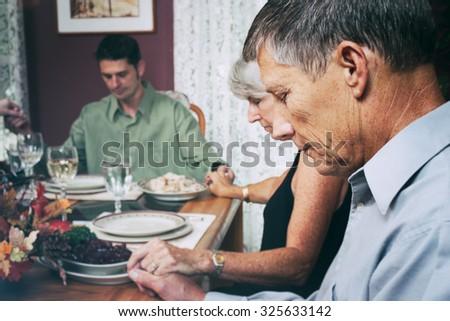 Thanksgiving: Family Says Prayer Before Dinner - stock photo