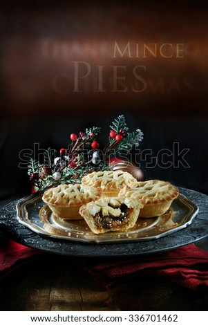 Thanksgiving or Christmas festive lattice pastry mince pies on antique pewter plate against a rustic background with accommodation for copy space. - stock photo