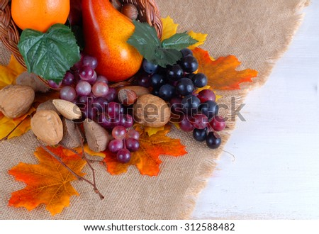Thanksgiving scene of cornucopia overflowing with purple grapes, a pear, and orange and nuts with golden autumn leaves scattered around on burlap background with space for your fall message - stock photo