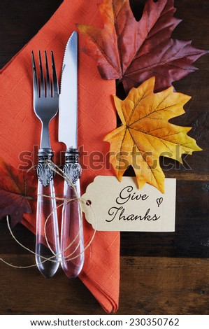 Thanksgiving table place setting with greeting tag, orange napkin, autumn fall leaves on rustic dark recycled wood background. Vertical. - stock photo