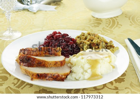 Thanksgiving turkey dinner with mashed potatoes and gravy, stuffing, and homemade cranberry sauce. Shallow depth of field. - stock photo