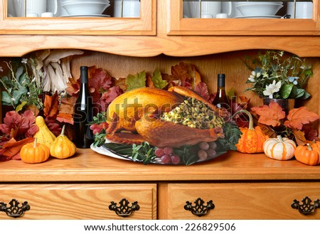 Thanksgiving turkey on a sideboard. The still life has fall leaves, pumpkins and decorative gourds wine bottles. The turkey is stuffed with garnish surrounding it on the platter. - stock photo