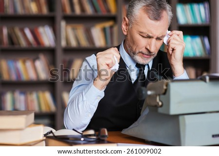 That is all wrong! Frustrated grey hair senior man in formalwear sitting at the typewriter and holding pieces of paper in his hands with bookshelf in the background