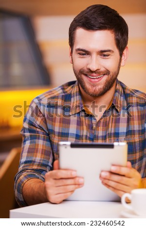 That is fun. Handsome young man looking at his digital tablet and smiling while sitting in coffee shop - stock photo