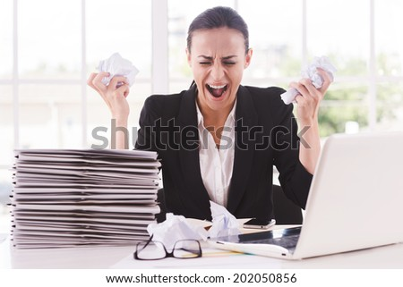That is too much for me! Furious young woman in formalwear holding papers in hands and shouting while sitting at her working place - stock photo