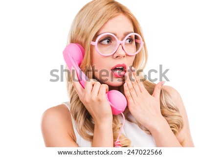 That is unbelievable! Frustrated young blond hair woman talking on the telephone and covering mouth with hand while standing isolated on white background