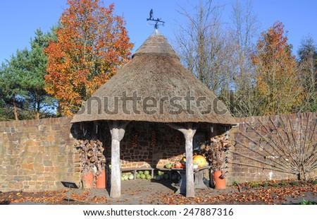 Thatch Roof Summerhouse in the Fruit and Vegetable Garden at Rosemoor, near Bideford, Devon, England, UK - stock photo