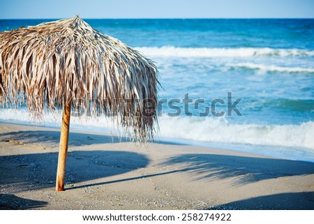 Thatch umbrella on beach - stock photo